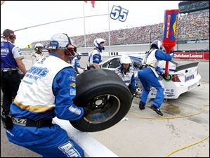 Brian Vickers' crew changes his tires during a pit stop.