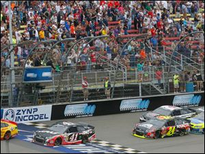 Cars make take a lap in front f the fans during the 45th Annual Pure Michigan 400 at Michigan International Speedway.