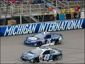 Jimmie Johnson takes over Cole Whitt on the track during the 45th Annual Pure Michigan 400.