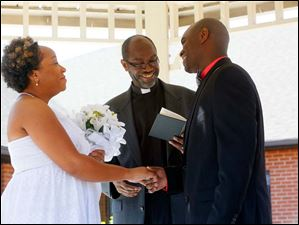 Pastor Robert Davis, the father of the groom, center, conducts the marriage ceremony between Miriam Reeves, left, and Mark Davis.