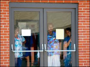 Care specialists with Foundation Park Alzheimer's Care peek out of the doors of the facility to watch Miriam Reeves being escorted down the aisle by her father.