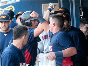 The Mud Hens' designated hitter Mike Hessman, center, is congratulated after his home run during the bottom of the second inning.
