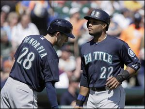 Seattle Mariners' Robinson Cano (22) is congratulated by Chris Denorfia (28) after scoring on a single by Kyle Seager.