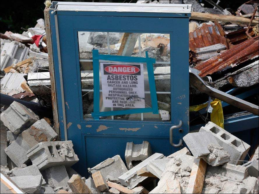 A door with an asbestos warning sticks out of the rubble.