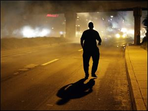 A man walks in the street after police fired tear gas to disperse a crowd Sunday during a protest for Michael Brown, who was killed by a police officer last Saturday in Ferguson, Mo.