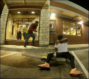 People leave a McDonald's restaurant after taking refuge from tear gas Sunday in Ferguson, Mo.