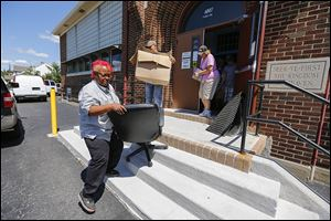 Jerrita Baker of Toledo carries out a chair she bought during an auction at the former Imani Learning Academy. It was one of the area charter schools that closed at the end of the academic year, and furniture and supplies were auctioned off to pay off their debts.