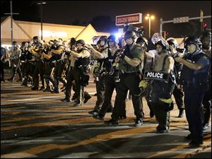 Police advance to clear people from the streets of Ferguson, Mo. Monday.