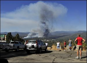 A fire creates a plume of smoke watched by onlookers along Highway 41 south of Oakhurst, Calif., Monday.