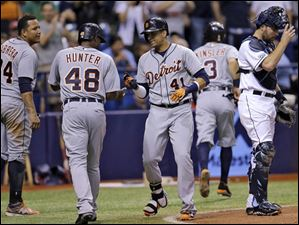 Detroit Tigers' Victor Martinez (41) celebrates with Miguel Cabrera (24), Torii Hunter (48), and Ian Kinsler after hitting a grand slam off Tampa Bay Rays relief pitcher Kirby Yates.