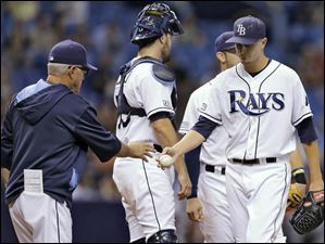 Tampa Bay Rays starting pitcher Jake Odorizzi, right, hands the ball to manager Joe Maddon after being taken out of the game.
