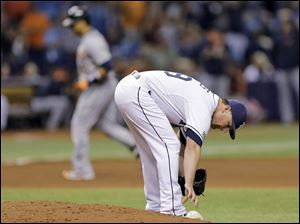 Tampa Bay Rays relief pitcher Kirby Yates reaches for the rosin bag as Detroit Tigers' Victor Martinez rounds the bases after hitting a grand slam.