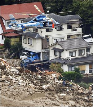 A survivor is lifted by a rescue helicopter from an area devastated by a massive landslide in western Japan.