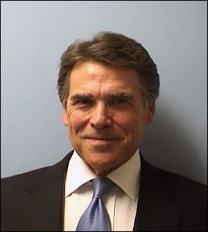 Texas Gov. Rick Perry smiles while being booked at the Blackwell-Thurman Criminal Justice Center in Austin, Texas, for two felony indictments of abuse of power on Tuesday.
