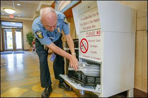 Toledo police officer Robert D'Agostino checks the drug drop-off box in the foyer of the Safety Building downtown on Erie Street.