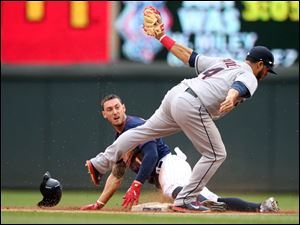 Minnesota Twins left fielder Jordan Schafer  loses his helmet as he is tagged out by Cleveland Indians shortstop Mike Aviles, right, during a steal attempt.