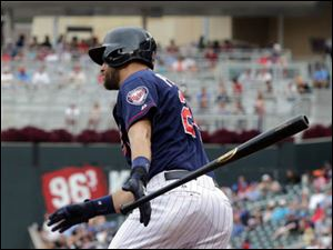 Minnesota Twins' Trevor Plouffe watches his two-run single off Cleveland Indians starting pitcher Corey Kluber.