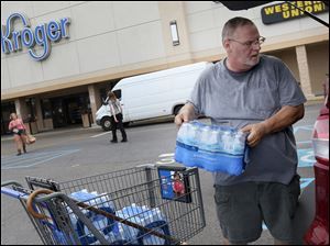 Jeff Rhoades of West Toledo loads bottled water into his car at the Kroger store on Monroe Street and Secor Road. Fears that Toledo drinking water is again unsafe were spreading Thursday leading many to stock up.
