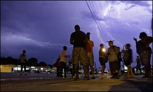 Protesters stand in the street as lightning flashes in the night sky in Ferguson, Mo. on W