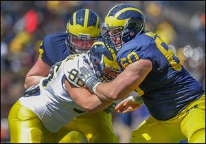 St. John's Jesuit grad Jack Miller, right, will start at center when Michigan opens its new season Aug. 30.