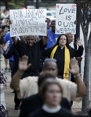 Protesters march to the Buzz Westfall Justice Center Wednesday in Clayton, Mo