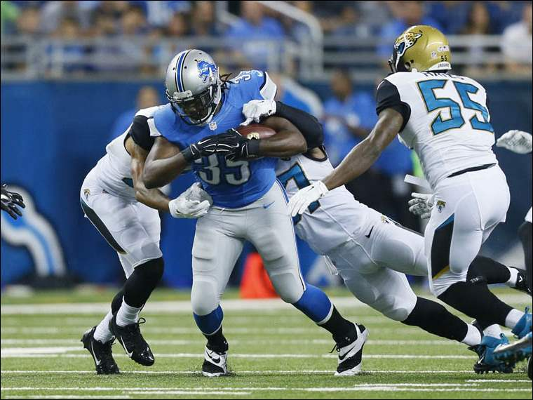 Detroit Lions running back Joique Bell (35) is brought down by Jacksonville Jaguars defenders.