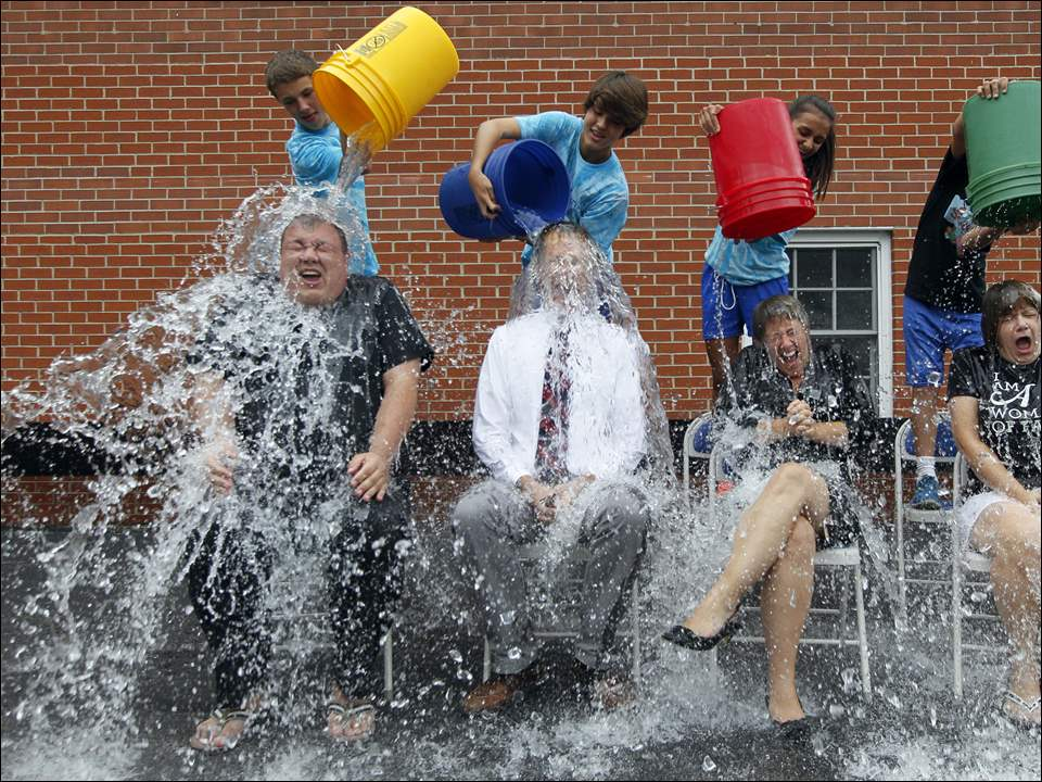 Left to right Father Jeff Walker, associate pastor at St. Rose Church in Perrysburg,  St. Rose School Principal Bryon Borgelt, Assistant Principal Keri Struckholz, and Administrative Assistant Kathleen Schramm have ice water dumped on them for the ALS Ice Bucket Challenge by eighth graders in back (left to right) Carter Higgins, 13, Justin Batdors, 13, Emily Spackey, 13, and seventh grader Noah Zak, 13.
