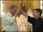 St. Joseph Maumee parish representative John Hoover, left, and Father Keith Stripe demonstrate the Mano Pa, a Philippine blessing.
