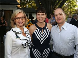 Chairman of the University of Toledo Women and Philanthropy Marianne Ballas, left, stands with Susan and Allan Block at their home. The Blocks hosted a dinner for the group, of which Mrs. Block is a member.