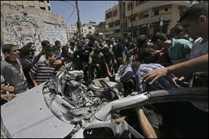 Palestinians inspect the wreckage of a vehicle following an Israeli airstrike at the main street in Gaza City in the northern Gaza Strip, Thursday.