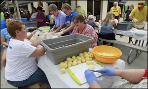 Volunteers peel potatoes — again — for potato salad at the festival after the first 1.5 ton-batch stored in a trailer was destroyed by fire.