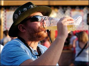 Cory Allarding of Oregon enjoys a beer at the 49th annual German-American Festival at Oak Shade Grove in Oregon. The festival, which opened Friday, continues through Sunday.