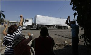 Ukrainian people greet the first truck as it passes the border post at Izvaryne, eastern Ukraine, today.