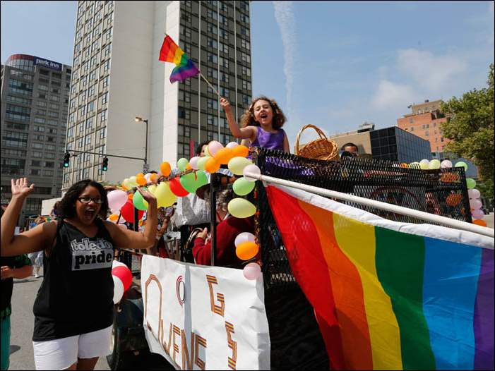 Lavern Brown walking alongside the Owens Community College's Gay Straight Alliance float at the Toledo Pride parade. On it, with the flag, is Jenna Addison. Both live in Toledo.