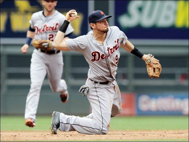 Detroit Tigers third baseman Nick Castellanos throws to first as shortstop Andrew Romine, left, backs him up.