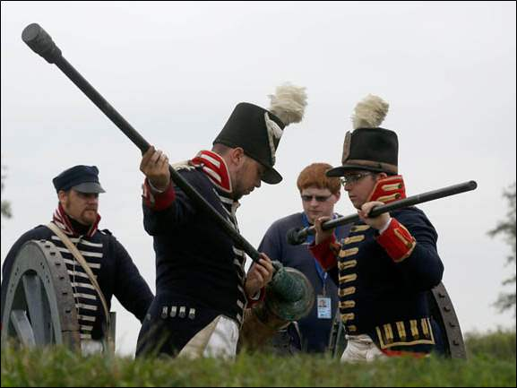 AJ Parks left, watches Aaron Gelb, front left, and Jarret Peart, front right, rehearse for a canon fire demonstration during the Life in Early Ohio event at Ft. Meigs in Perrysburg, Ohio. The soldiers are from the 7th Infantry.