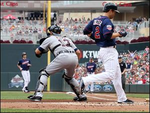 Minnesota Twins' Brian Dozier, right, scores on a Joe Mauer, left, single off Detroit Tigers pitcher Buck Farmer in Game 1.