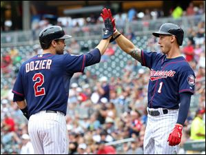 Minnesota Twins' Brian Dozier, left, and Jordan Schafer celebrate after they scored on a Joe Mauer double off Detroit Tigers pitcher Buck Farmer in Game 1.