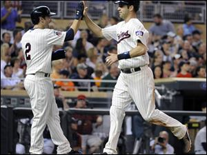 Minnesota Twins Joe Mauer, right, celebrates with Brian Dozier (2) after scoring on a double hit by Trevor Plouffe against Detroit Tigers.