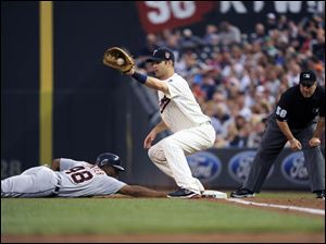 Detroit Tigers Torii Hunter, left, is safe at first as Minnesota Twins first baseman Joe Mauer tries to pick him off.