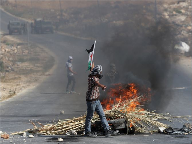 Palestinian protesters face Israeli soldiers during clashes, following a protest against the Israeli military action in Gaza.