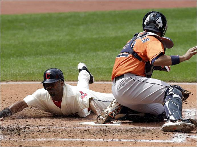 Cleveland Indians' Michael Bourn, left, slides safely into home plate as Houston Astros catcher Carlos Corporan is late on the tag.