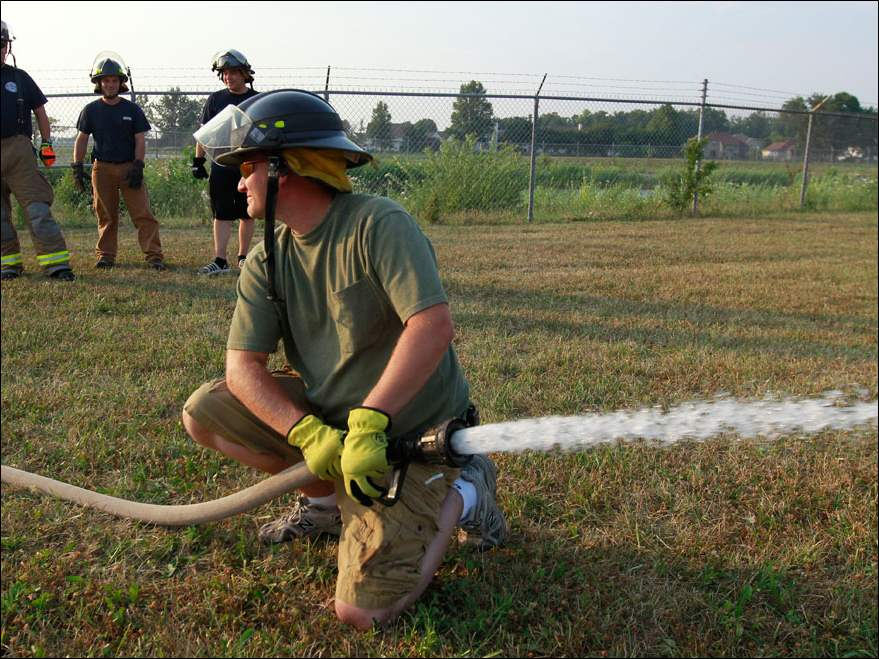 Waterville volunteer fireman John Cannon purges air from a fire hose during their weekly training.