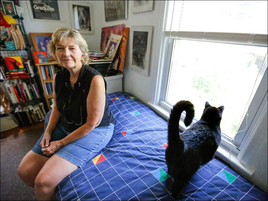 Lylanne Musselman sits with her cat Graham near the window where burglars broke into her home.  Besides losing some valuables, she nearly lost Graham when he somehow ended up outside.