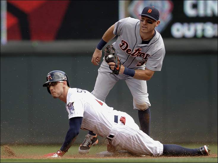 Minnesota Twins' Jordan Schafer, left, slides in with a double as Detroit Tigers second baseman Ian Kinsler, right, attempts the tag.