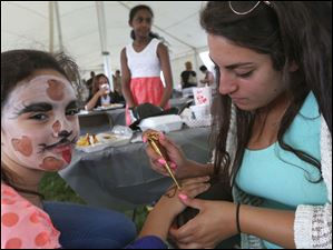 Lydia Kamel, 7, left, has henna applied to her hand by Angie Jacob of Perrysburg.