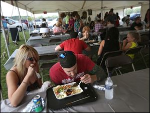 Maumee residents Audra Fisher, left, and Ian Dawson share a plate of traditional Egyptian food.