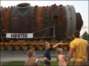 Cole, 10, center left, asks his father Anthony Parasiliti, right, a question as join Cole's brother Tony, 8, left, and sister Mackenzie, 7, center right, watch a reactor and third stage separator as they move by the Deep South Heavy Lift and Transport Solutions company along Front Street in East Toledo.