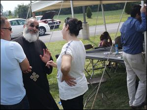 Hesham Youssef, left, and Mira Guirgis, right, talk with Father John Ragheb.