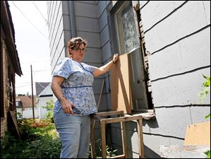 Nancy Grove holds the boards that were secured to the window to her kitchen before burglars broke into her home through the window on Aug. 6, 2014.